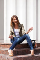 Happy young fashion woman sitting on the steps