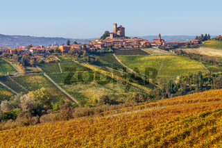 Small town and yellow vineyards in Piedmont, Italy.