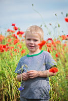 Positive boy in field with red poppies
