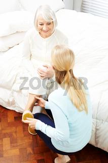 Enkelin hilft Oma beim Hausschuhe anziehen