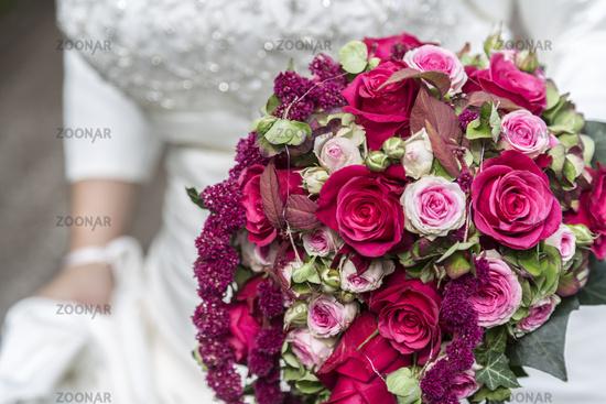 Bridal bouquet on white wedding dress
