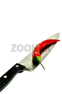 Messer mit roter Chili freigestellt vor Weiß