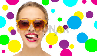 happy young woman in sunglasses showing tongue