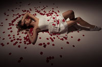 beauty brunette woman wearing white dress and rose petals