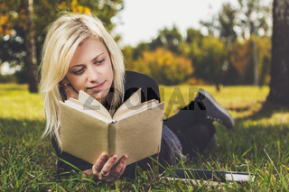 girl reading in park on grass