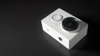 Abstract action camera on black background, unrecognizable brand model, copy-space