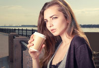 Pensive young trendy woman drinking take away coffee and standing leaning back granite fence urban scene.