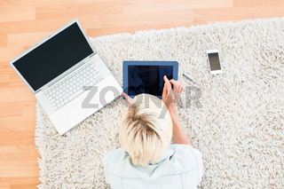 Pretty blonde woman lying on the floor and using her tablet