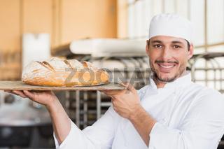 Baker holding a freshly baked loaf