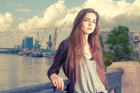 Lonely girl waiting for your. Wearing light gray shirt, black jacket, an young american woman standing by metal fence on pier in New York, frowned, port cranes on background. Instagram effect.