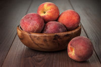 wooden bowl with some peaches on the table