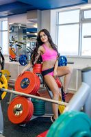 In gym. Beautiful brunette posing with barbell