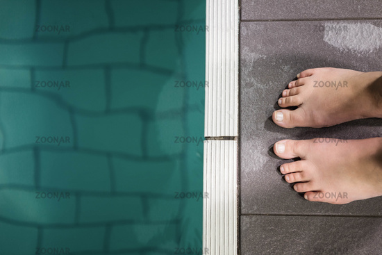 Feet of woman standing on the edge of the pool