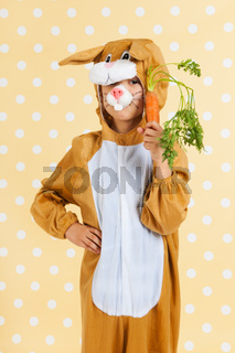 Child as easter hare with carrot