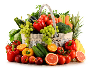Variety of organic vegetables and fruits in wicker basket isolated on white