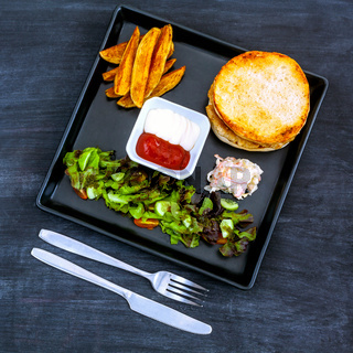 Tasty homemade burger with  lettuce, onion and tomatoes on blackboard.