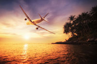 Airplane flying over amazing tropical sunset landscape. Thailand travel destinations