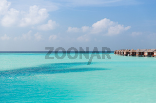 bungalow huts in sea water on exotic resort beach