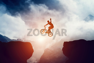 Man jumping on bmx bike over precipice in mountains at sunset. Raising hand showing hello gesture. Extreme sport