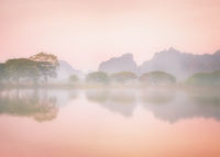 Foggy morning with trees reflection in lake. Hpa An, Myanmar