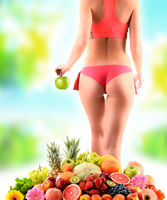 Weight loss. Slim woman holding an apple and composition with variety of fresh fruits.