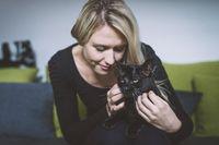 A young blond woman fondles a black cat's fur.