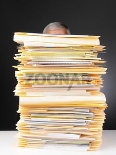 Businessman Behind Stack of Files