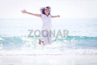 Carefree woman jumping on the beach