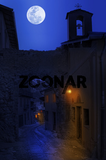 Night view of narrow street in small town.