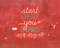 'Start where you stand' painted on a wall