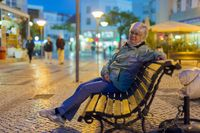 An elderly lady sitting in the evening on a bench in the city. Camera views.