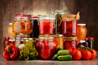 Jars with pickled vegetables and fruity compotes. Preserved food