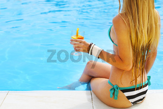 Pretty blond woman enjoying cocktail near the swimming pool