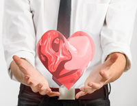 Red glass heart in businessman hands