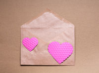Two pink hearts on craft paper envelop