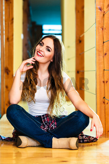 girl in denim trousers sitting on floor
