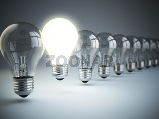 Idea or uniqueness, originality concept. Row of light bulbs with glowing one on blue background,