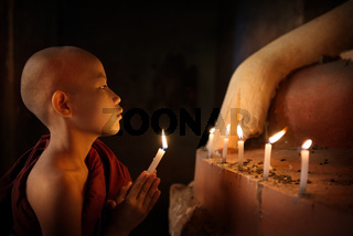Buddhist novices praying with candlelight in temple