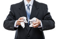 Angry businessman hand holding crumpled torn paper