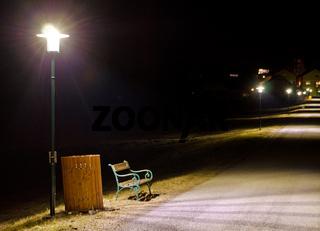 Sitzbank und Abfallkübel bei Nacht
