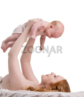 Pretty red-haired mother playing with her baby