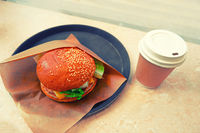 American burger and takeaway cup of coffee on table toned image top view