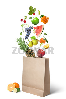 Fruits falling into bag isolated on white
