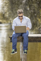 man at the lake with notebook