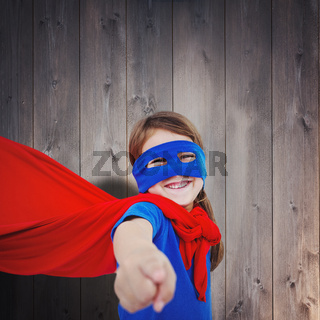 Composite image of smiling masked girl pretending to be superhero