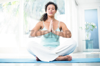 Pregnant woman sitting on exercise mat with hands joined