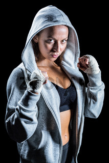 Portrait of female boxer in hood with fighting stance