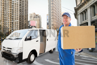 Composite image of happy delivery man showing cardboard box