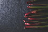 Fresh rhubarb on dark stone with beautiful light