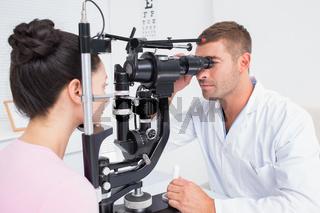 Optician examining female patients eyes through slit lamp